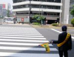 Yellow_flag_man_for_Road_crossing_safety_in_Japan